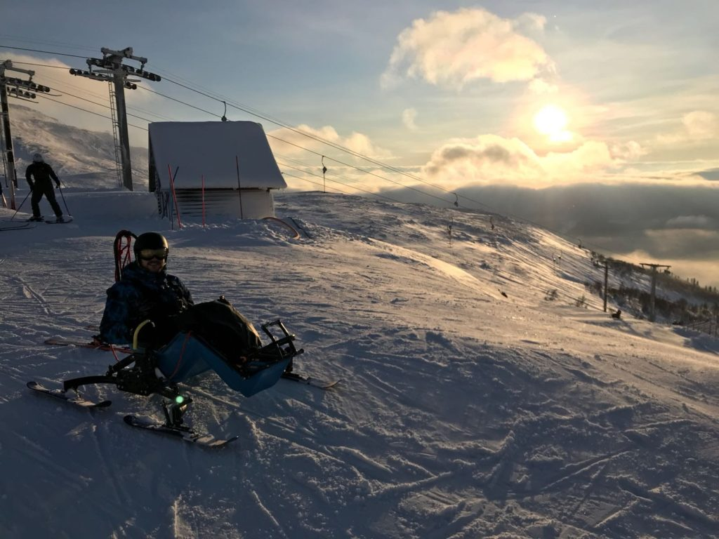 Ski-Karter on a ski top with sunny scenery in the background