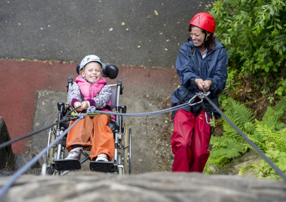 Young girl abseiling in her wheelchair at a Back Up Under 13s activity course