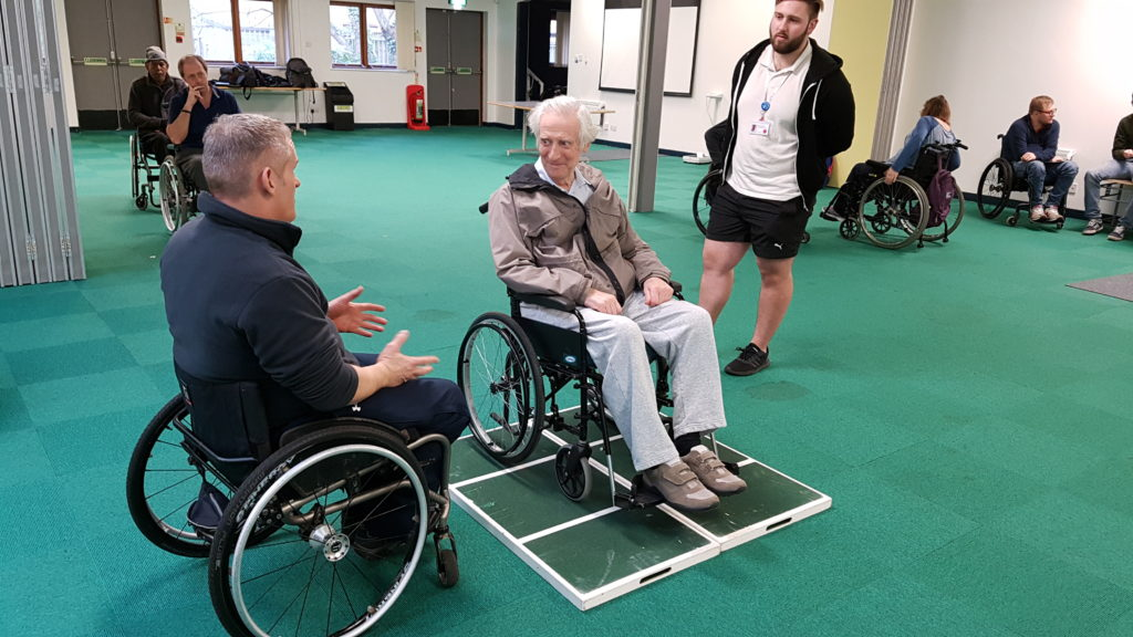 Wheelchair skills trainer teaching a new technique to a participant