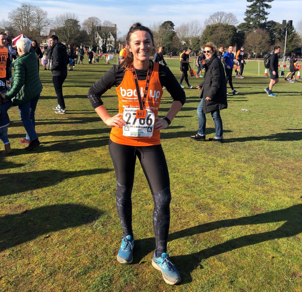 Melanie, wearing a Back Up vest, posing with her medal after the Hampton Court half marathon