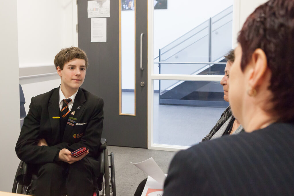 KEvin, a young person with a spinal cord injury, talking to a teacher