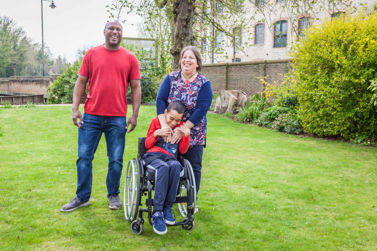 A family with a young boy with a spinal cord injury in a garden
