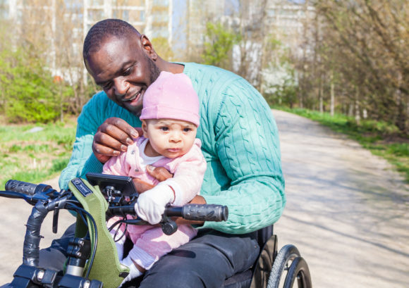 Shaun, a wheelchair user, is playing with his newborn daughter in a park