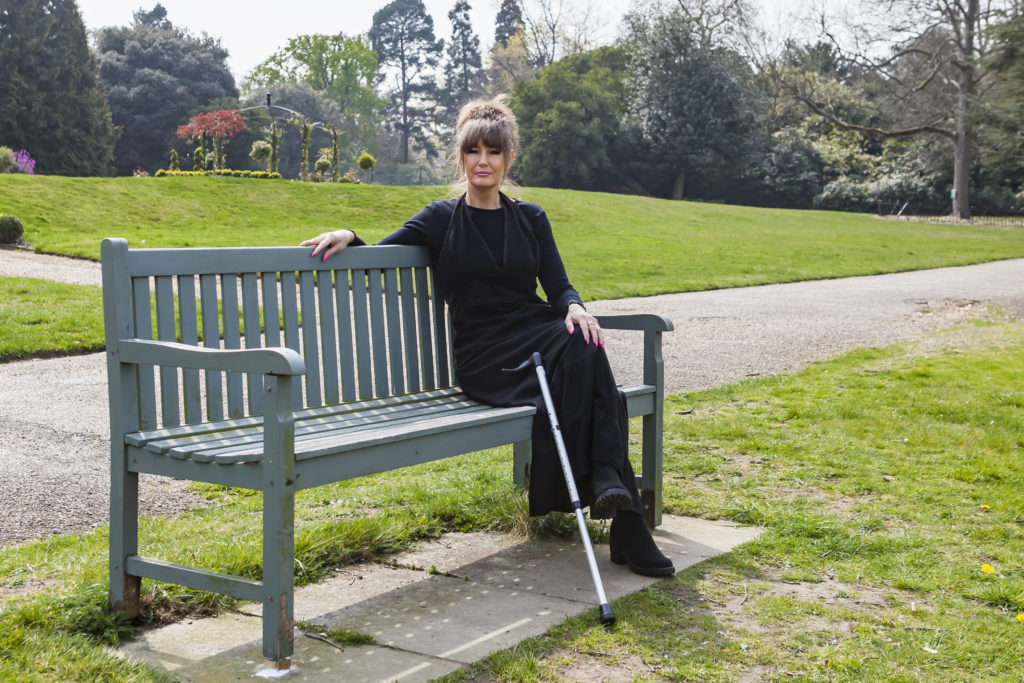 Tina, who experiences pain after spinal cord injury, sitting outside on a bench