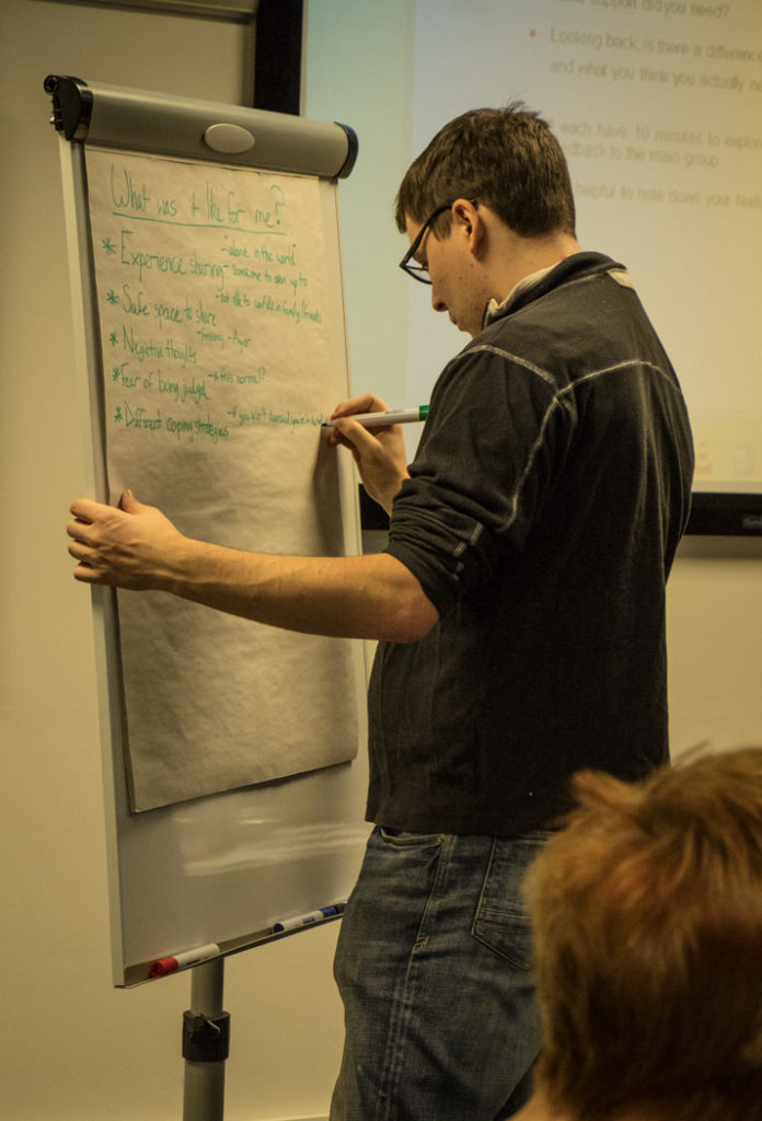 Andrew writes on a flipchart at a mentor training weekend