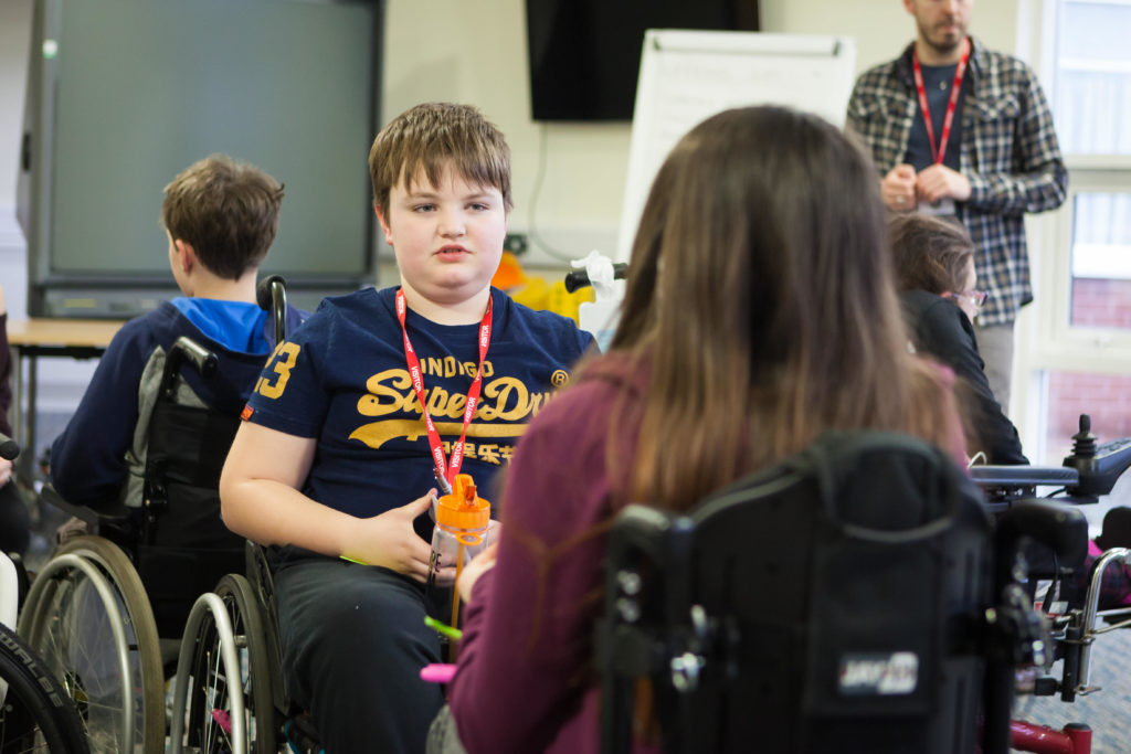 Young wheelchair users having a discussion at a training weekend
