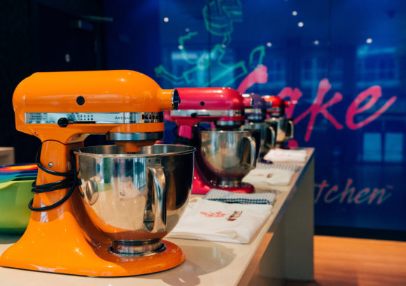 A row of standing mixers for cake making in front of a wall with the Cake Boy logo on