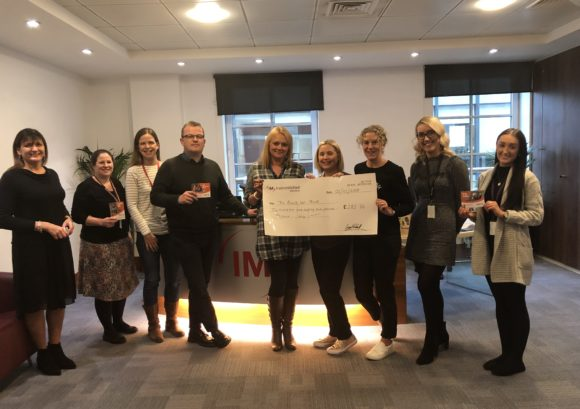 Members of the Irwin Mitchell Serious Injury team holding up a big cheque for the £282.76 they raised for Back Up