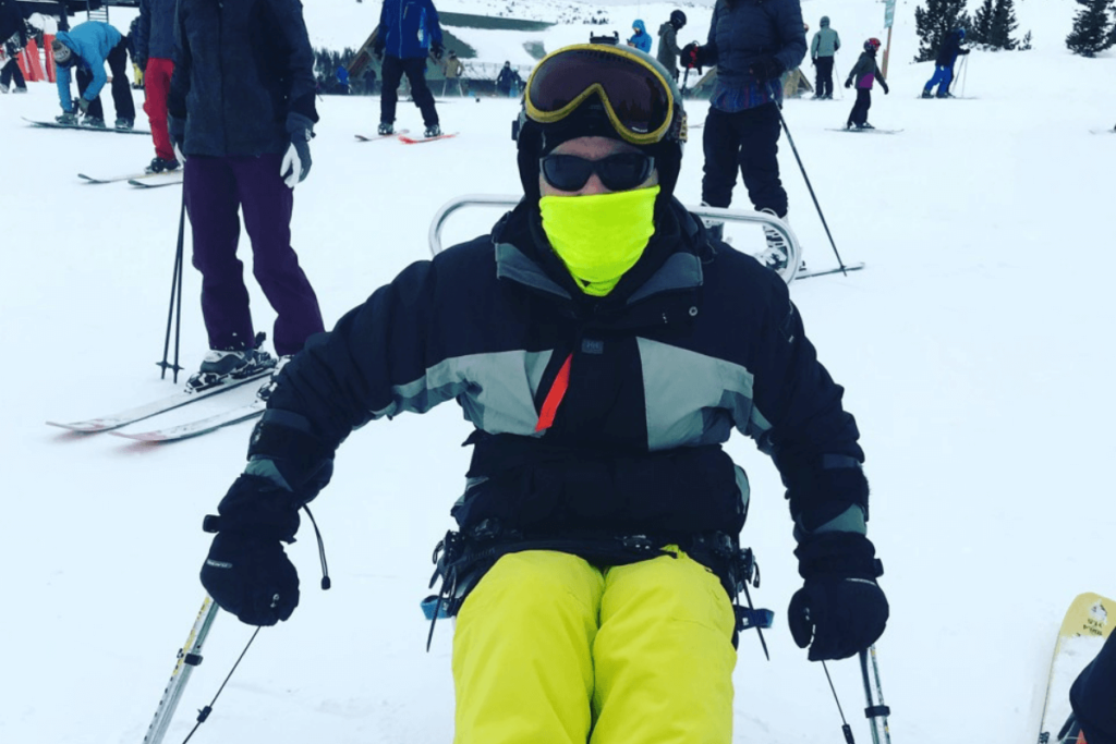 Ian using a sit ski during some travel after spinal cord injury