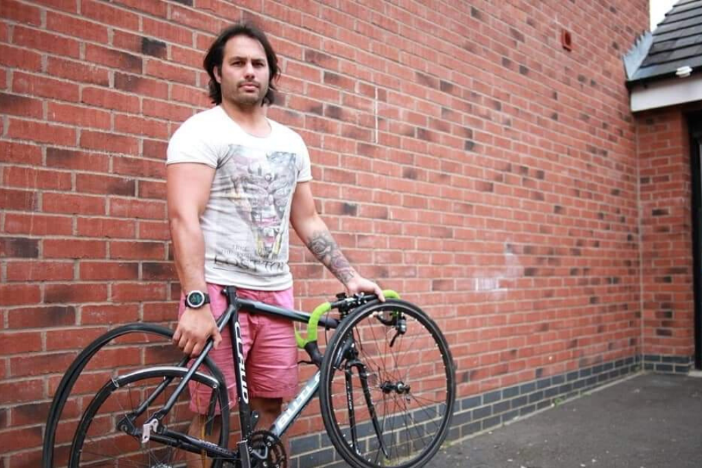 Adrian posing by a wall with a bike