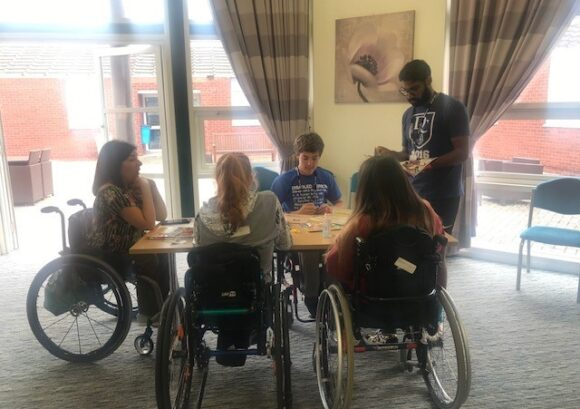 a group of young wheelchair users around a table