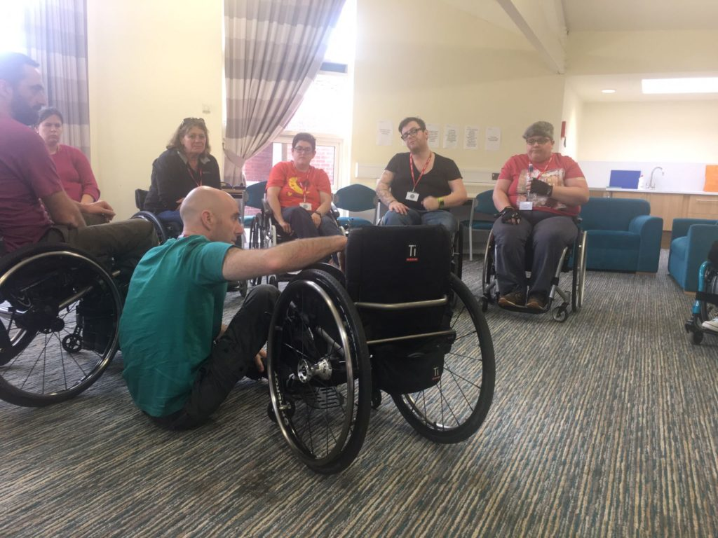 Trainer demonstrating floor to chair transfer on Skills for Independence course