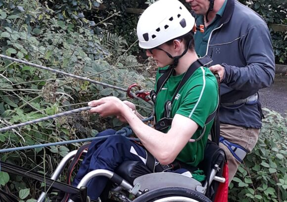 A young wheelchair user abseiling with a volunteer supporting