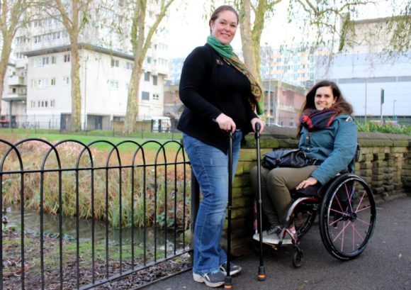 Two people with a spinal cord injury smiling in a park