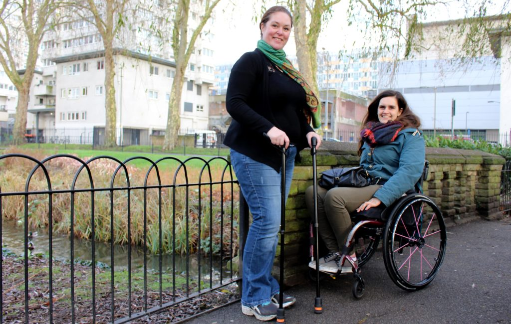 Someone walking with aids and a wheelchair user