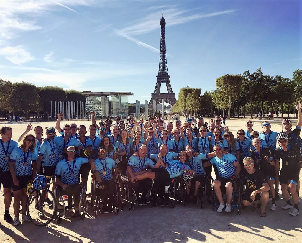 The triumphant London to Paris team pose in front of the Eiffel Tower after finishing the ride