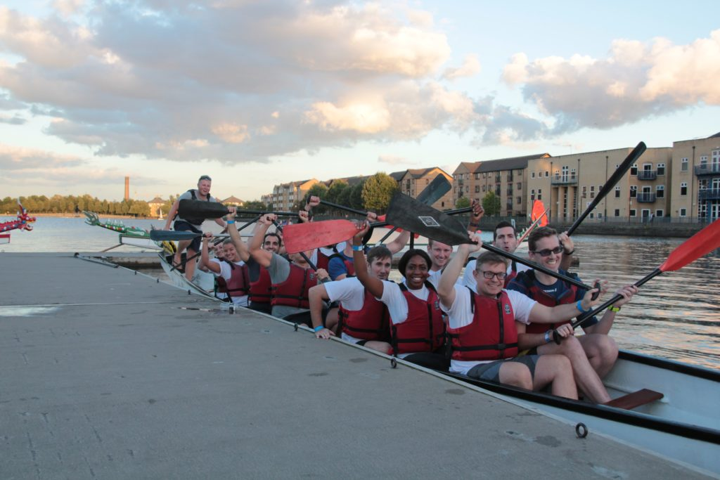 A group of people sitting in a boat raising their oars in the air.