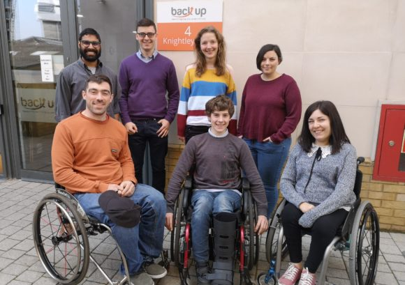 Kevin, a young spinal cord injured person, posing for a group photo with the Back Up staff during his work experience week