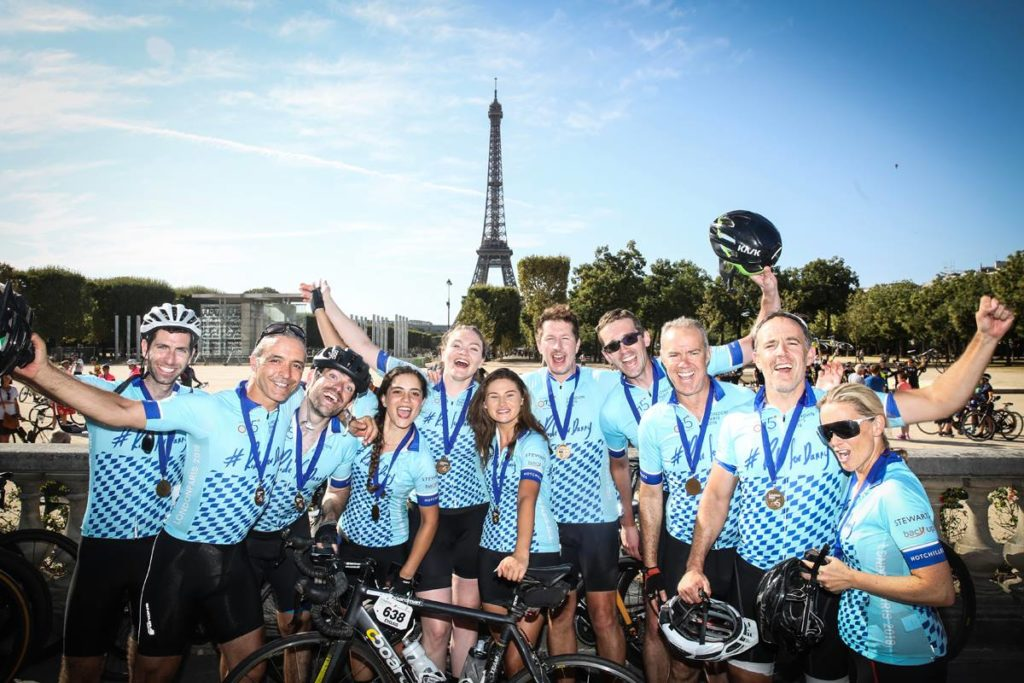 A group of our London to Paris cyclists celebrating reaching the finish line of the cycling challenge.