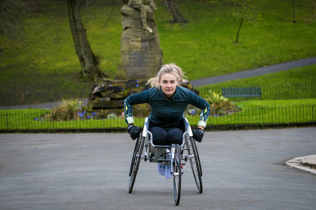 Photo of Melanie exercising in her racing chair - the featured image in her Three Marathons story