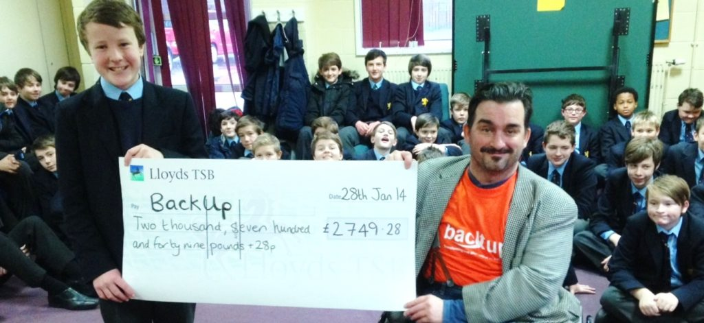 School pupil and person in a Back Up top presenting a cheque for Back Up