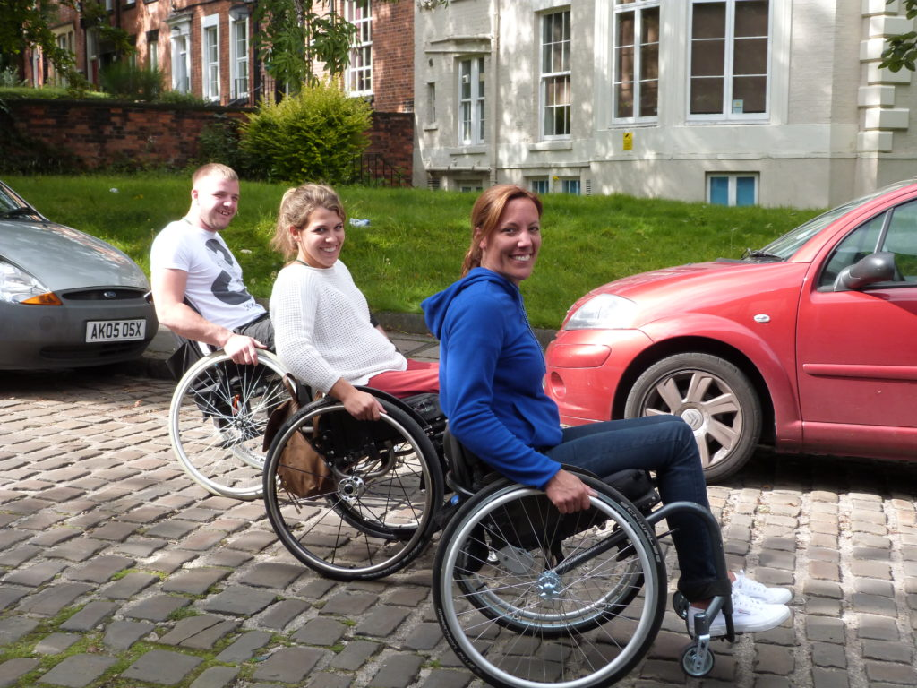 Three wheelchair users on a course
