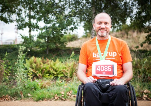 Wheelchair user with medal at a fundraising challenge