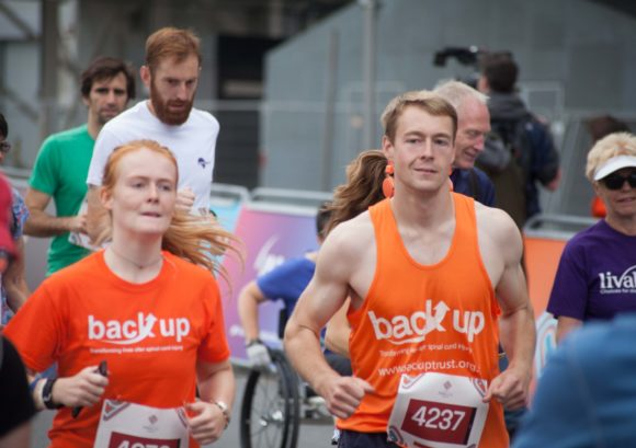 Two competitors running side by side in a race supporting Back Up