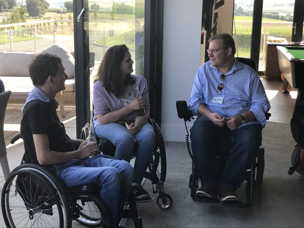 Two manual wheelchair users and a powerchair user having a chat