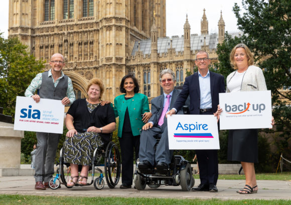 The CEOs and chairs of Back Up, Aspire, and SIA stood together outside the house of commons holding banners with the names of each charity