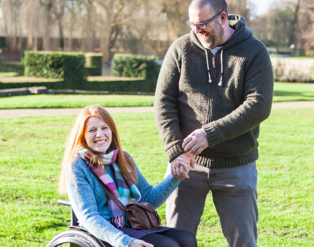 A family member with their wife who has a spinal cord injury in a park