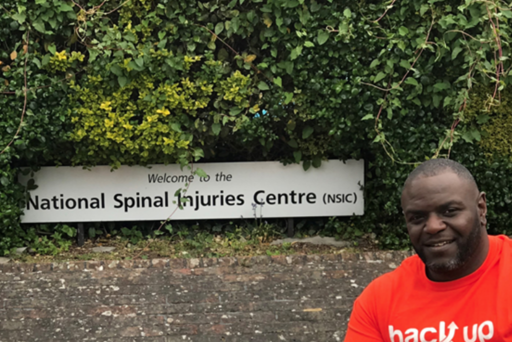 Shaun, our first ever Back Up Star, posing with the sign outside the National Spinal Injuries Centre, Stoke Mandeville