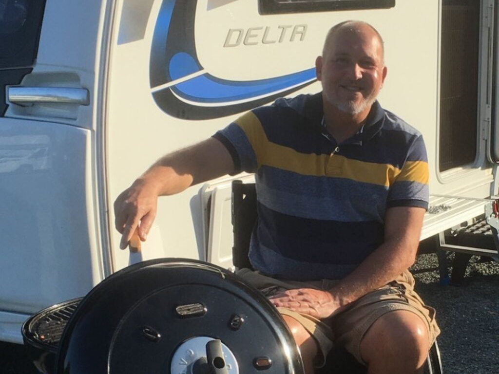 Steve, a wheelchair user, sat in front of his caravan, cooking on a BBQ