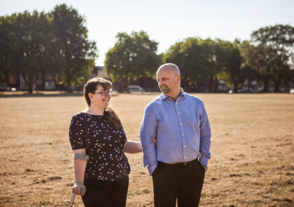 Chloe, a person with a spinal cord injury who can walk, standing in a field with her partner.