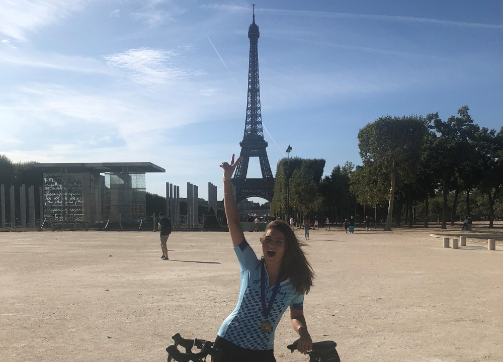 Lauren celebrating in front of the Eiffel Tower after completing the #RideforDanny cycling challenge