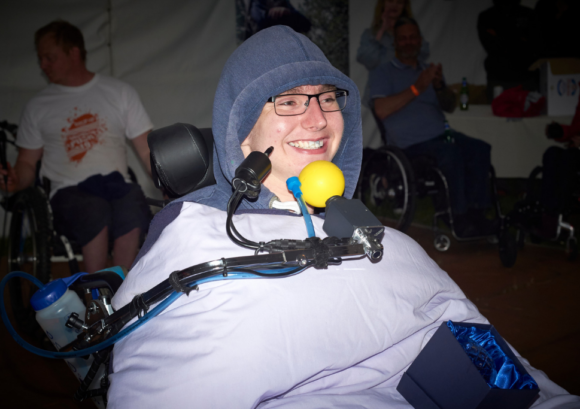 "Peter, a chin controlled power chair user, grinning after winning the ""spirit of the push"" award at our annual Snowdon Push challenge."