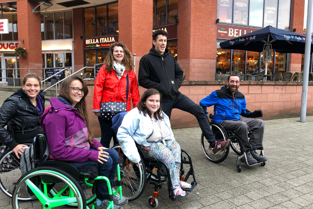 Laura, a young volunteer, posing with a group of wheelchair users