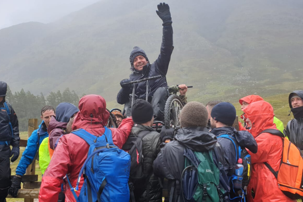 Andrew, a wheelchair user, being lifted over a fence during the Ben Nevis push