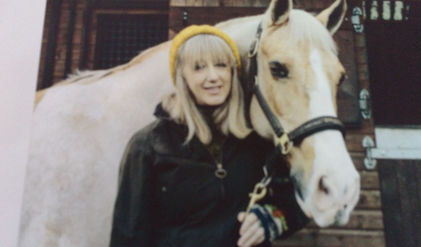 Jill, someone with an incomplete spinal cord injury who can walk without aids, posing with a horse