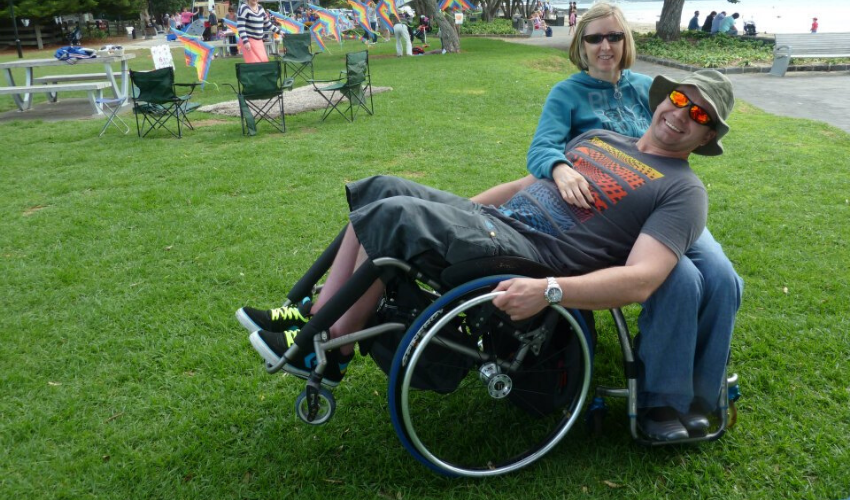 Jacques, someone with an incomplete spinal cord injury who uses a manual wheelchair, on holiday with his wife