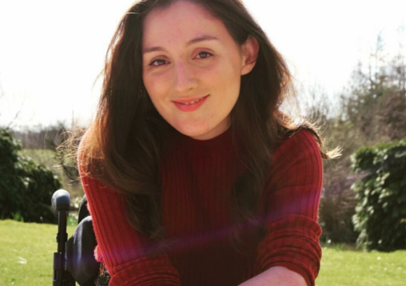 Emma @Sittingdownstyle, a wheelchair user model, posing for a photo in the sun