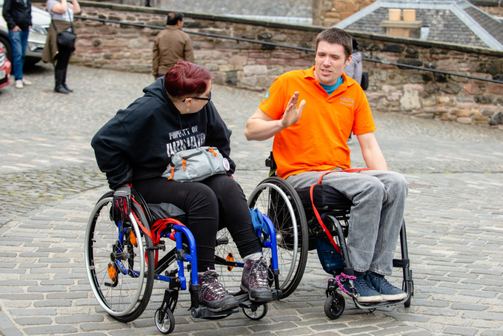 Two wheelchair users on a cobbled street - you can learn how to tackle obstales like this using our wheelchair skills app