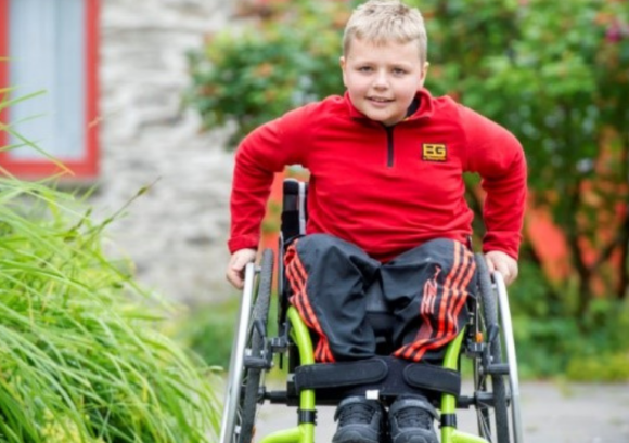 A YOUNG WHEELCHAIR USER PUSHING TOWARDS THE CAMERA