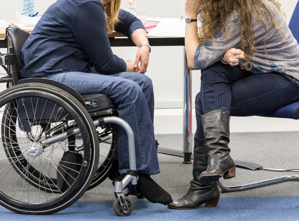 Two women talk by a table. One of them is a wheelchair user.