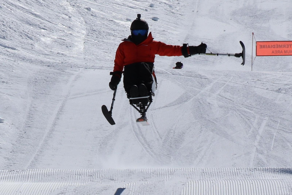 David going over a jump using a sit ski