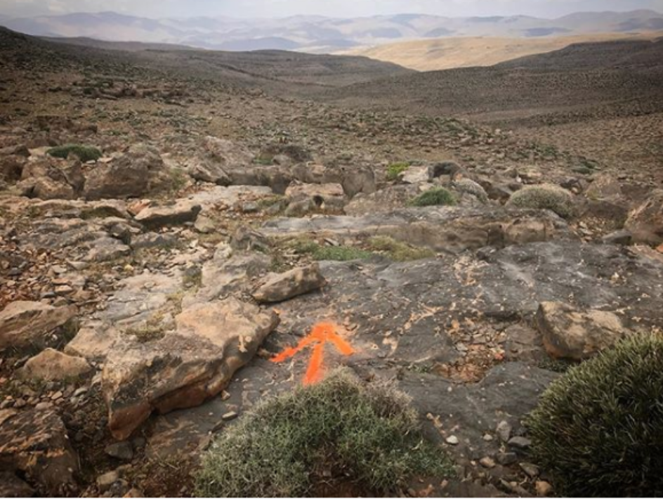 A rocky part of the ultra marathon path with an orange arrow marking the way