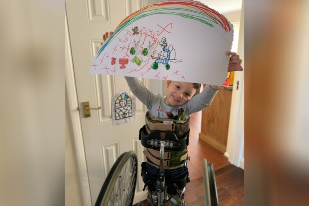 A young wheelchair user holding up a rainbow painting. this giving tuesday, you can help even more young people