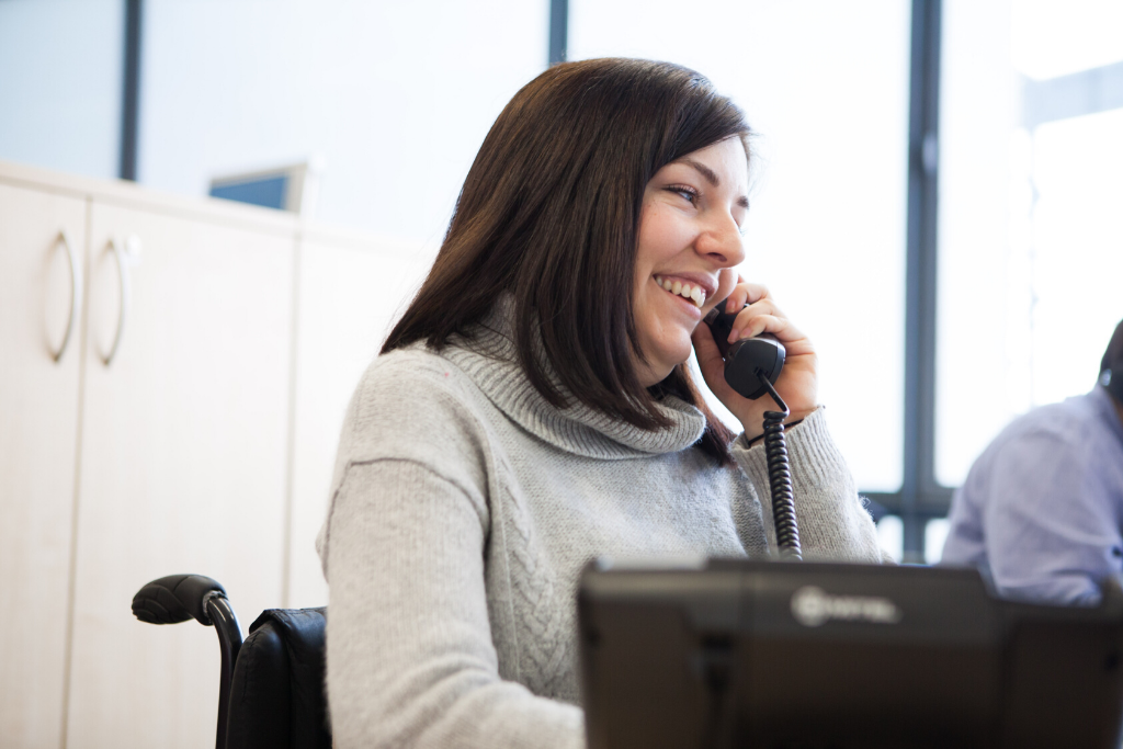 Ella, a wheelchair user who has a personal assistant, answering the phone in the Back Up office
