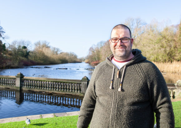 Richard, one of our family mentor volunteers, stood by a lake on a sunny day