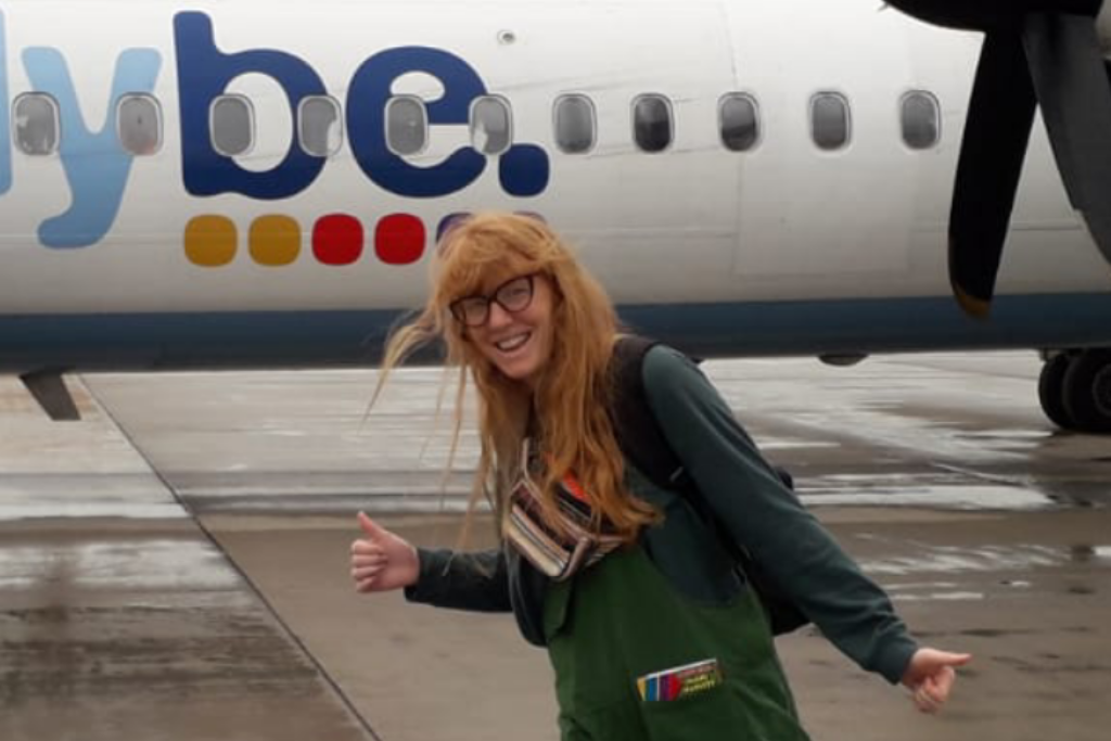 Holly, a spinal cord injured person who can walk without aids, posing in front of a plane